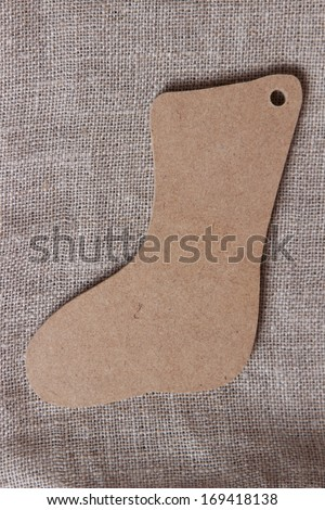 Christmas background with a closeup of a symbolic christams wooden boot over burlap background on Holiday theme - stock photo