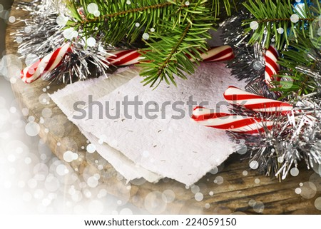 Christmas background with a red and white candies, fir branches with blank paper on wooden planks, wooden table background, New year theme - stock photo