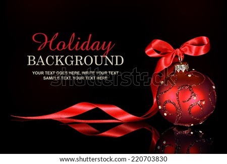 Christmas background with a red ornament and ribbon on a black background - stock photo