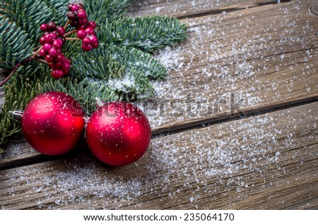 Christmas background with a red ornament, berries and fir in snow - stock photo