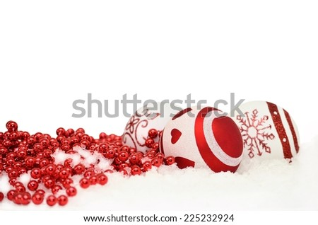 Christmas background with baubles and red garland in snow on white - stock photo