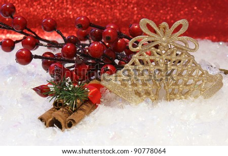 Christmas background with berries, cinnamon and bells nested in snow