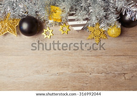 Christmas background with black, golden and silver decorations on wooden table. View from above with copy space - stock photo