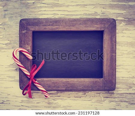 Christmas background with candy canes and framed blackboard - stock photo