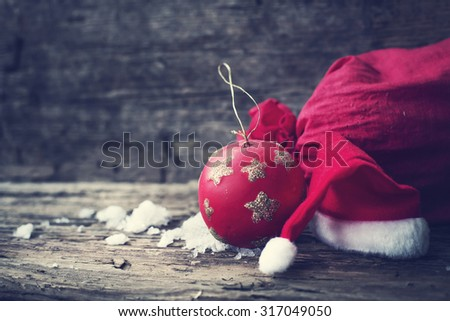 Christmas background with christmas ball, gift, red hat and snow on a wooden background/ Christmas background - stock photo
