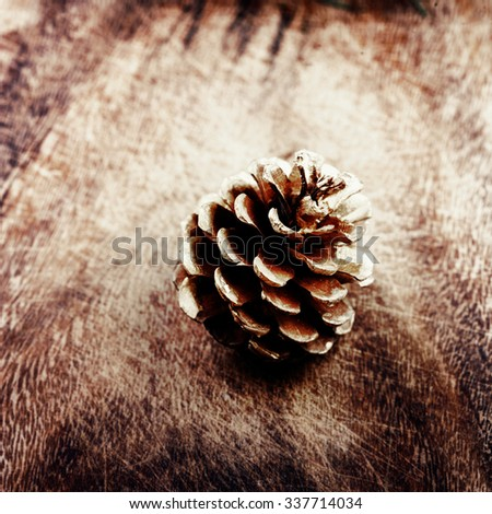 Christmas background with christmas decoration. Festive pine cone over wooden board. Card or invitation.