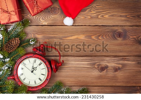 Christmas background with clock, snow fir tree and gift boxes over wood - stock photo