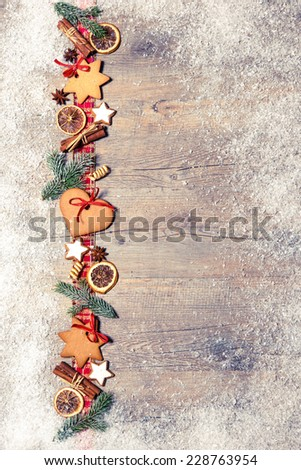 Christmas background with cookies, fir branches and spices on the old grunge wooden board - stock photo
