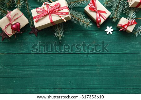 Christmas background with copyspace over rustic green wooden boards with a top border of decorative gifts and pine branches - stock photo