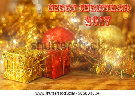 Christmas background with decorations and gift boxes on wooden board. Beautiful blurred glowing background with bokeh