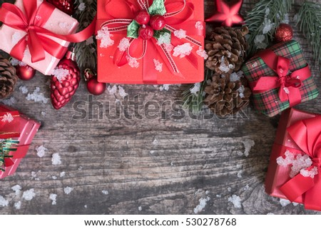 Christmas background with decorations gift boxes and red ornament on rustic wooden table