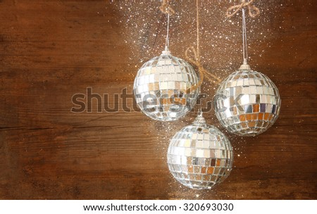 christmas background with decorations  hanging on a rope over wooden background. glitter overlay - stock photo