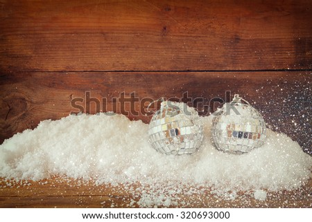 christmas background with decorations  on snow over wooden background. glitter overlay - stock photo