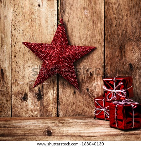 Christmas background with festive decorations on old wooden wall. Old fashioned Christmas red star and gift boxes  with copyspace. - stock photo