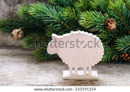 Christmas background with fir branch and wooden toy sheep - stock photo