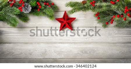 Christmas background with fir branches on a bright wooden board and a red star hanging in the middle - stock photo