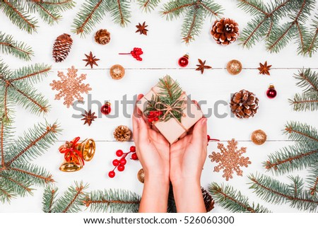 Christmas background with fir branches, pine cones, red decorations. Female hands holding Christmas gift. Xmas and Happy New Year composition. Flat lay, top view