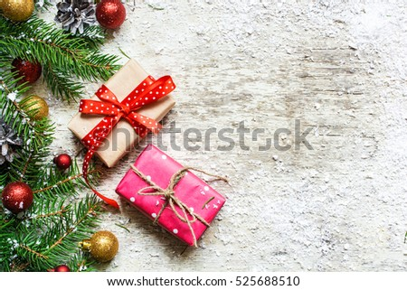 christmas background with fir tree, decorations and gift boxes covered with snow on white wooden background