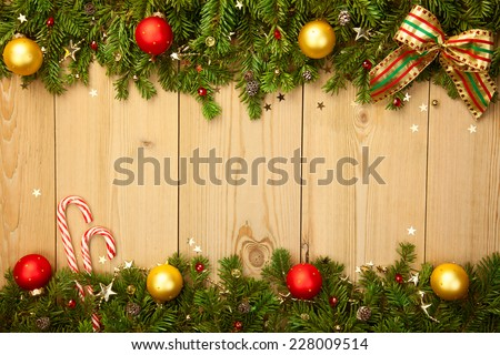 Christmas background with firt-ree, candies, baubles and stars on wood  - stock photo
