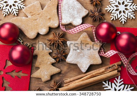 Christmas background with gingerbread cookies, cinnamon sticks, anise and baubles.
