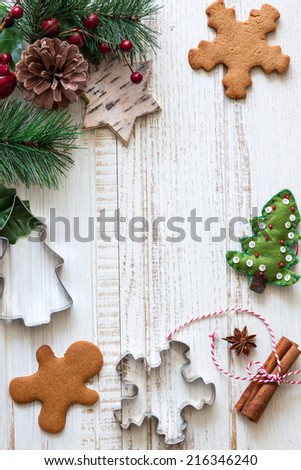 Christmas background with gingerbread,cookies cutters,fir  branches and spices on the old wooden board - stock photo