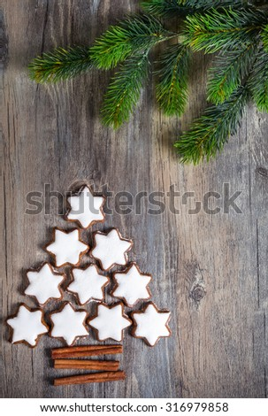 Christmas background with gingerbread cookies,fir branches and spices on the old wooden board. - stock photo
