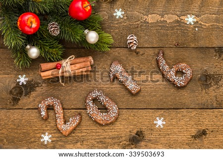 Christmas background with gingerbread numbers 2016, fir branches and decorations on the old wooden board.