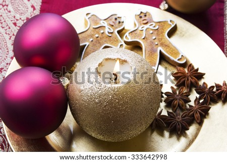 Christmas background with golden candle, baubles and gingerbread cookies - stock photo