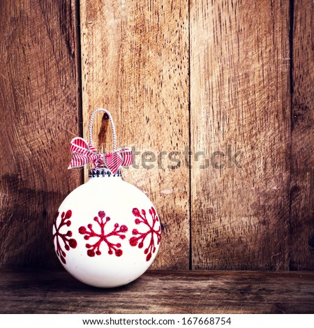 Christmas background with holiday decorations  over wooden board.  Vintage Christmas card with copyspace. White festive bauble and red ribbon.  - stock photo