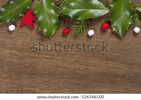 Christmas background with Holly leaves and berries on a wooden background.
