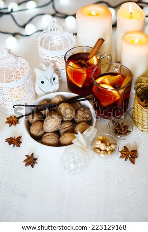 Christmas background with mulled wine, walnuts, candles and white decorations. Shallow dof, selective focus. Space for your text.