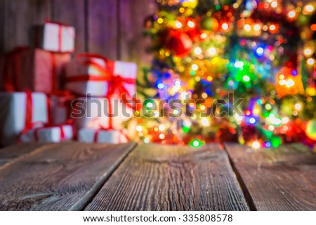 Christmas background with old wooden table, light bokeh and presents. - stock photo