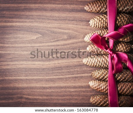 Christmas background with pinecones and a red Christmas ribbon/ Christmas decoration with Pine Cone and snow - stock photo