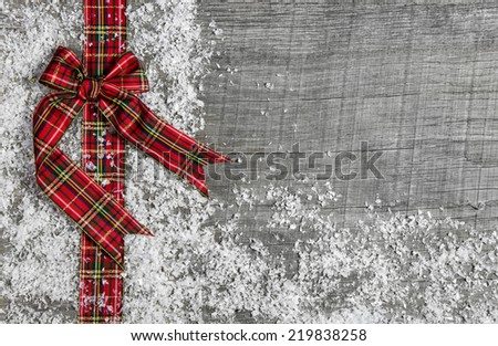 Christmas background with red green checked ribbon on wood. - stock photo