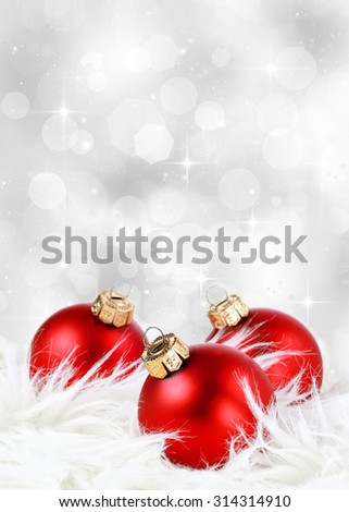 Christmas background with red ornaments on feathers against a festive sparkling silver background - stock photo