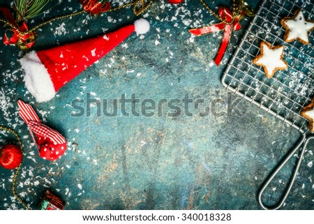 Christmas background with Santa hat, snow , red winter decoration and star cookies, top view, border - stock photo