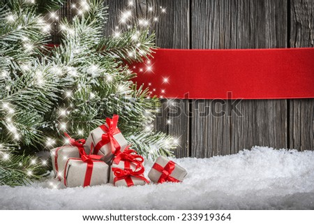 Christmas background with small gifts, red ribbon and spruce branch - stock photo