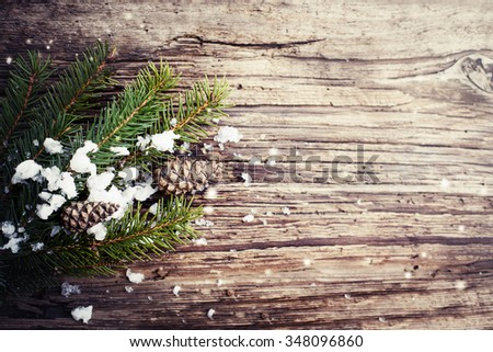 Christmas background with snow,fir/ christmas tree branches over wooden background - stock photo