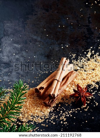 Christmas background with traditional spices with a bundle of stick cinnamon and star anise on scattered caramelized brown sugar scattered on a dark surface with copyspace and decorated with pine - stock photo
