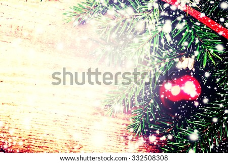 Christmas Background with Tree Branch on wooden board  with festive ribbon and red bauble . Christmas ornaments with copy space for greeting text, close up. - stock photo