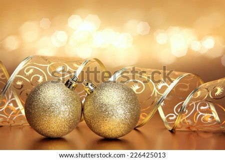 Christmas background with two golden ornaments, ribbon and bokeh