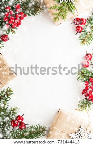 Christmas background with xmas tree, red berries on white wooden background. Merry christmas greeting card, frame, banner. Winter holiday theme. Happy New Year. Space for text. Flat lay. Snow effect.