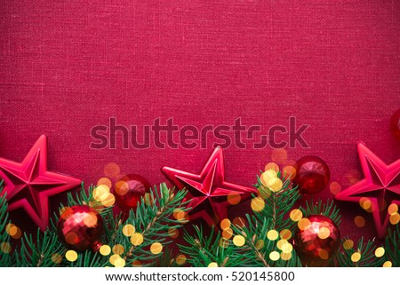 Christmas background with xmas tree, red ornaments and glowing golden bokeh lights on red canvas background. Merry christmas card. Winter holiday theme. Space for text. Happy New Year.