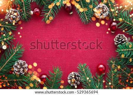 Christmas background with xmas tree, red ornaments and glowing golden bokeh lights on red canvas background. Merry christmas card. Winter holiday theme. Happy New Year. Space for text.