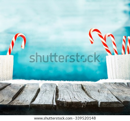 Christmas background. Wooden table with candy cane on snow. Empty winter display for your montage - stock photo