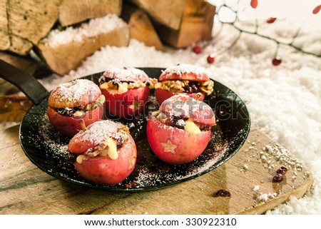 Christmas baked stuffed fresh red apples with a star decoration and raisin and walnut stuffing sprinkled with sugar on a pan outdoors on a rustic wooden board in winter snow - stock photo
