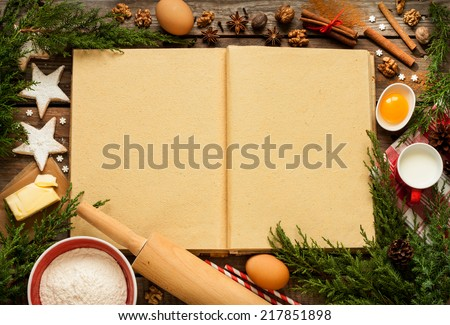 Christmas - baking cake background. Blank opened cook book with food ingredients and decorations around on vintage planked wood table from above. Layout with free text space. - stock photo
