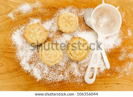 Christmas baking. Home made mince pies on a scratched wooden table covered with icing sugar, next to sieve and metal teaspoon. Snow flake shape pattern on mince pies. - stock photo