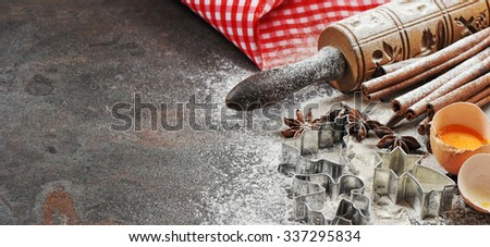 Christmas baking ingredients and tolls for dough preparation. Flour, eggs, rolling pin and cookie cutters - stock photo