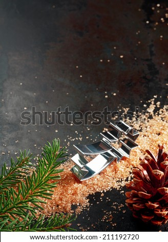 Christmas baking still life with a star shaped cookie cutter and caramelized sugar on a dark background with a decorative pine cone and fresh green pine branch, with copyspace in vertical format - stock photo
